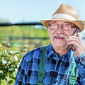 Senior Gardener Talking On The Phone With A Client. by Michal Bednarek