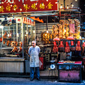 Shop Owner Standing In Front Of Poultry Shop On Temple Street Night Market Kowloon Hong Kong China by Ruurd Dankloff
