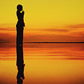 Silhouette Of A Girl Practicing Yoga Reflected On The Surface Of Water During Beautiful Sunset by Srdjan Kirtic