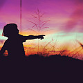 Silhouette Of A Playful Boy Pointing With Finger In The Field During Beautiful Sunset by Srdjan Kirtic