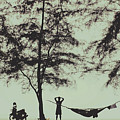 Silhouette Of A Young Men With Crossed Hands Above His Head Camping Hammocking In The Nature by Srdjan Kirtic
