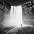 Single Tourist At Skogafoss Waterfall In Iceland by Joe Fox