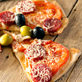 Slices Of Homemade Pizza With Salami by Vadim Goodwill