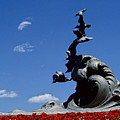 Statue And Tulips Against A Clear Blue by Kenneth Garrett