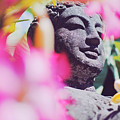 Stone Carved Statue Of Buddha Surrounded With Colorful Flowers Bali, Indonesia by Srdjan Kirtic