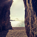 Sun Glinting Through A Cave At Bussaglia Beach In Corsica by Jon Ingall