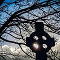 Sun Shining Through Celtic Cross Famine Monument by James Truett