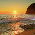 the beach and the Mediterranean sea in Montenegro in the summer at sunset by George Westermak