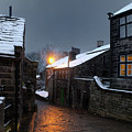 The Village Of Heptonstall In The Snow At Night With Lamps Shini by Philip Openshaw
