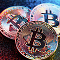 Three Bitcoin Coins In A Colorful Lighting. by Michal Bednarek