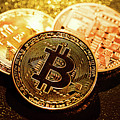 Three Golden Bitcoin Coins On Black Background. by Michal Bednarek