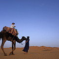 Touareg Man Leading Boy Riding Camel In Sahara Desert by Sami Sarkis