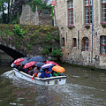 Tourists With Umbrellas In A Sightseeing Boat On The Canal In Bruges by Louise Heusinkveld