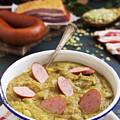 Traditional Dutch Pea Soup And Ingredients On A Rustic Table by Sara Winter