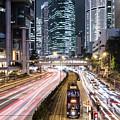 Traffic Rushing In Hong Kong Island While A Tram Car Wait. by Didier Marti