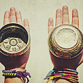 Two Hands Holding And Showing Both Sides Of Decorated Tibetan Singing Bowls by Srdjan Kirtic