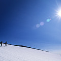 Two Hikers Explore A Snowfield by Bill Hatcher