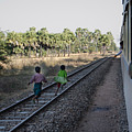 Two Kids Run Along And Follow Train In Burma by Jason Rosette