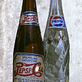 Two Pepsi Bottles On A Table by Daniel Hagerman