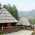 Village With Wooden Cabin Log On Mountain by Goce Risteski