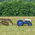 Vintage Ford Blue And White Tractor On A Farm by Edward Fielding