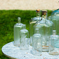 Vintage Glass Bottles On Table by Andreas Berthold