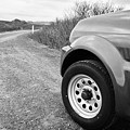 Wheel Of Small 4x4 Vehicle Driving On Gravel Road Onto Main Road Reykjavik Iceland by Joe Fox