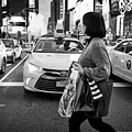 woman crossing crosswalk in front of yellow cabs in the evening in Times Square New York City USA by Joe Fox