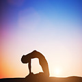 Woman In Camel Yoga Pose Meditating At Sunset by Michal Bednarek