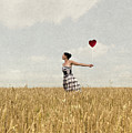 Woman In Corn Field With Heart Shaped Balloon by Clayton Bastiani