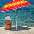 Woman In Red Bikini And White Hat Under Parasol Looking Out To S by Jon Ingall