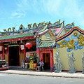 Woman Sits Outside Chinese Temple With Urn And Deity Statues Pattani Thailand by Imran Ahmed