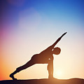 Woman Standing In Revolved Side Angle Yoga Pose Meditating At Sunset by Michal Bednarek