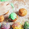Woman's Hand Coating A Donut With Green Frosting. by Michal Bednarek