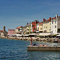 Young Couple Fishing Reading Sunbathing On Dock At Piran Sloveni by Reimar Gaertner