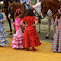 Young Girls In Flamenco Dresses Looking At Horses At The April F by Reimar Gaertner