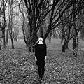Young Woman With Her Head Tilted Back While Standing In A Forest by Alexandre Rotenberg