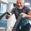 Senior Man Exercising With Ropes At The Gym. by Michal Bednarek