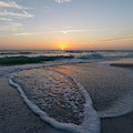 The Sunset Turns The Sky Orange And Yellow Along The Beach On An by William Kuta