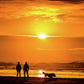 A Couple Walking Their Dog At Sunset On Ynyslas Beach, Wales Uk by Keith Morris