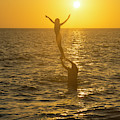 A Father Lifts His Daughter Out Of The Water Along The Beach At  by William Kuta