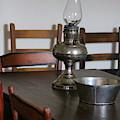 Antique Hurricane Lamp On Table by Colleen Cornelius