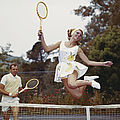 Couple On Tennis Court, Woman Jumping by Tom Kelley Archive