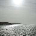 Low Tide Sandy Beach Ripples Silhouetted Against Sun by Unknown