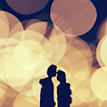 Romantic Couple Kissing On Illuminated Background. by Michal Bednarek