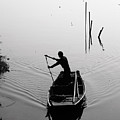 Silhouette Of A Boatman Rowing A by Gwoeii