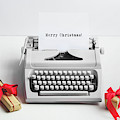 Typewriter With Merry Christmas Text And Gifts by Michal Bednarek