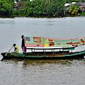 Weathered Boat With Sailor And Passenger And Solar Panel Crosses Sarawak River Kuching Malaysia by Imran Ahmed