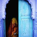 Woman Sitting Near Blue Door by Dave Rawlinson