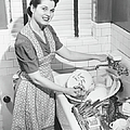 Woman Washing Dishes In Kitchen Sink by George Marks